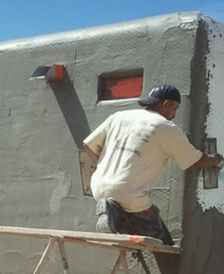 Man putting stucco on home